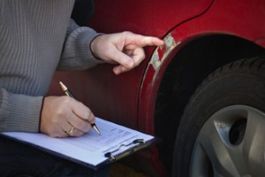 Person with clipboard taking notes while inspecting damage on vehicle