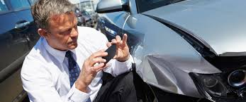 Man taking photo with cell phone of damage to car from collision